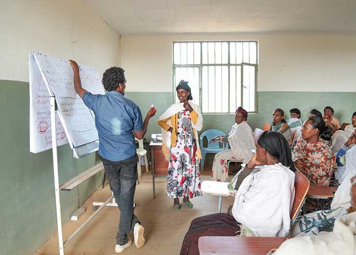 Lehrer steht in Schule in 'Äthiopien und unterrichtet Erwachsene Frauen