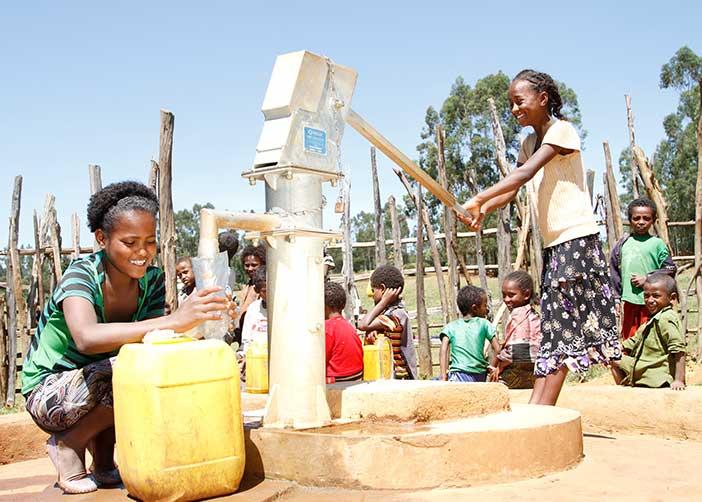 Zwei Mädchen in Äthiopien bei einem Brunnen holen Wasser