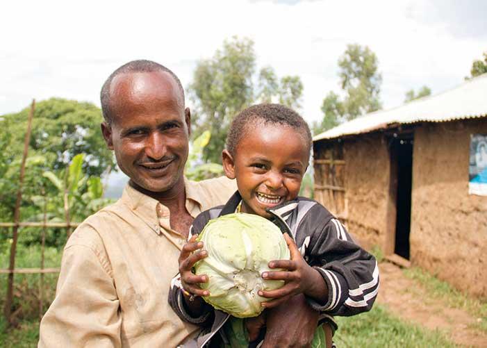 Mann mit Sohn im Arm der einen Kohl hält in Äthiopien