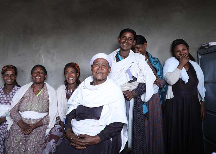 Frauen einer Kreditgruppe in Äthiopien stehen und sitzen