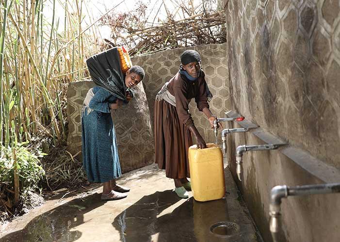 Zwei Frauen holen Wasser an neuer Quelle von mensche für Menschen in Äthiopien