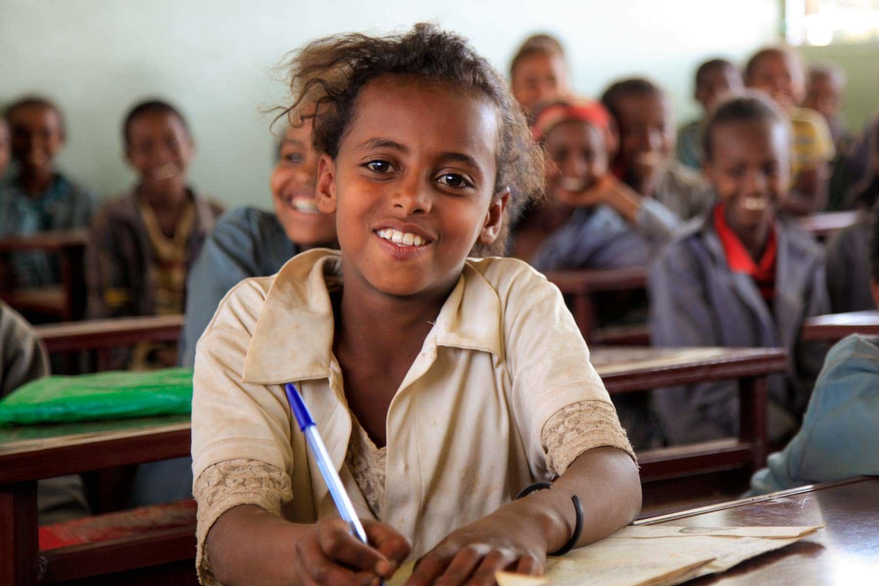 Mädchen sitzen in dunkler Schule in Äthiopien und lächeln