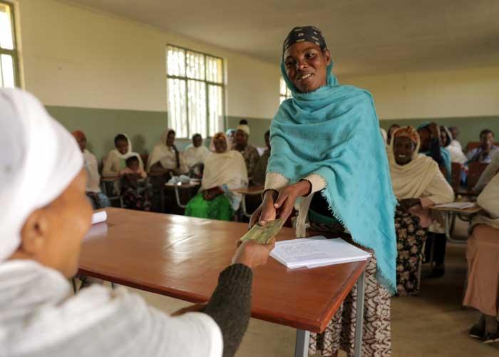 Frau erhält Geld aus ihrer Mikrokreditgruppe