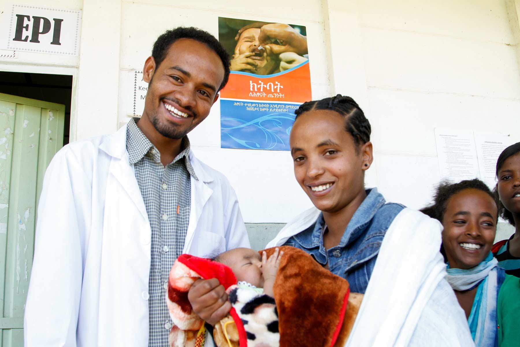 Doktor und Patientin lächeln in die Kamera mit Kind im Arm