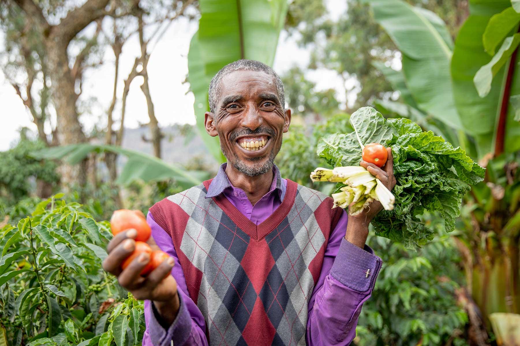 Mann lächelt und hält Gemüse in den Händen