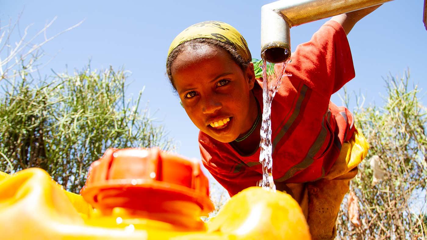 Frau an befestigter Wasserquelle von Menschen für Menschen holt Wasser