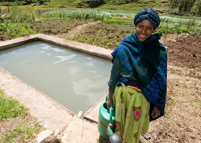 Frau vor Bewässerungsanlage von Menschen für Menschen