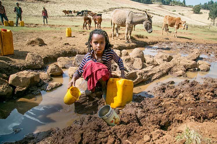 Junges Mädchen in Äthiopien beim Wasserholen an ungeschützter quelle