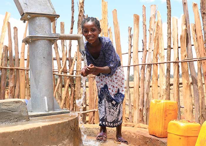 Junges Mädchen in Äthiopien beim Wasserholen in befestigter Quelle von Menschen für Menschen