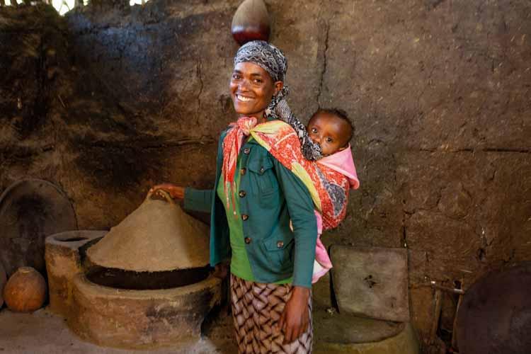 Frau mit Baby auf dem Rücken bei ihrem holzsparenden Ofen