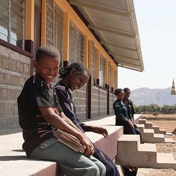 Kinder sitzen vor einer neuen Schule in Äthiopien von Menschen für Menschen