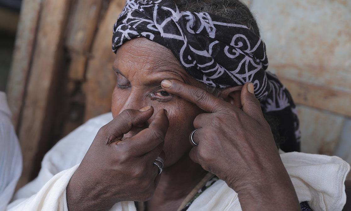 Frau zupft sich die Wimpern aus