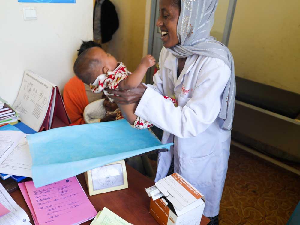 Krankenschwester hält Kind im Arm in Äthiopien