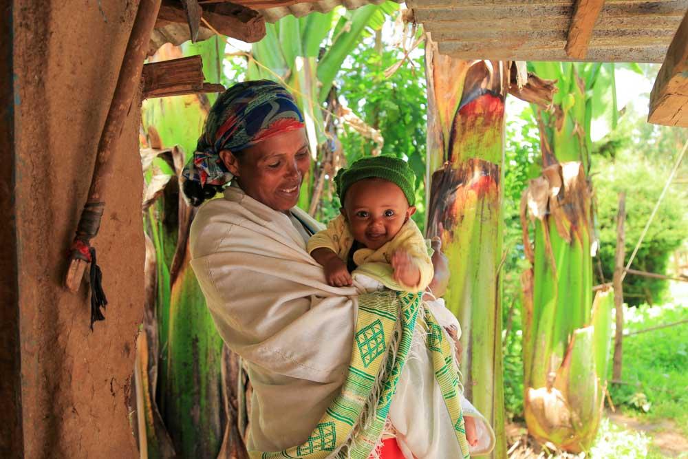 Mutter mit lächelndem Kind im Arm in Äthiopien