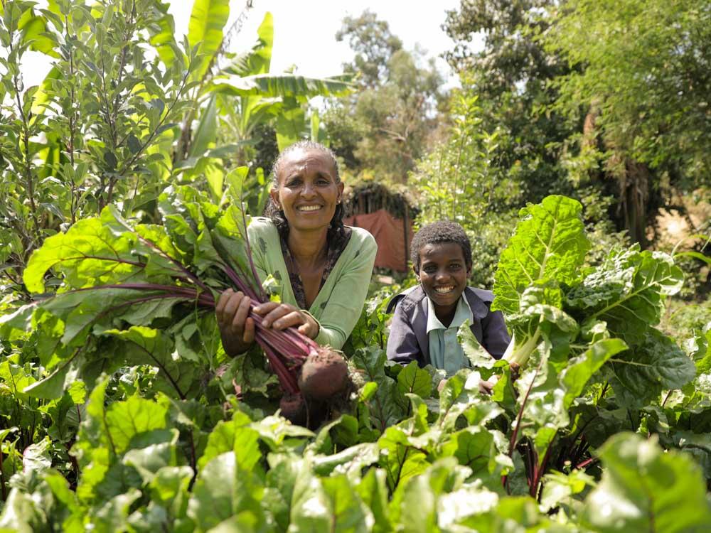 Mutter und Sohn knien lächelnd im Gemüsebeet in Äthiopien
