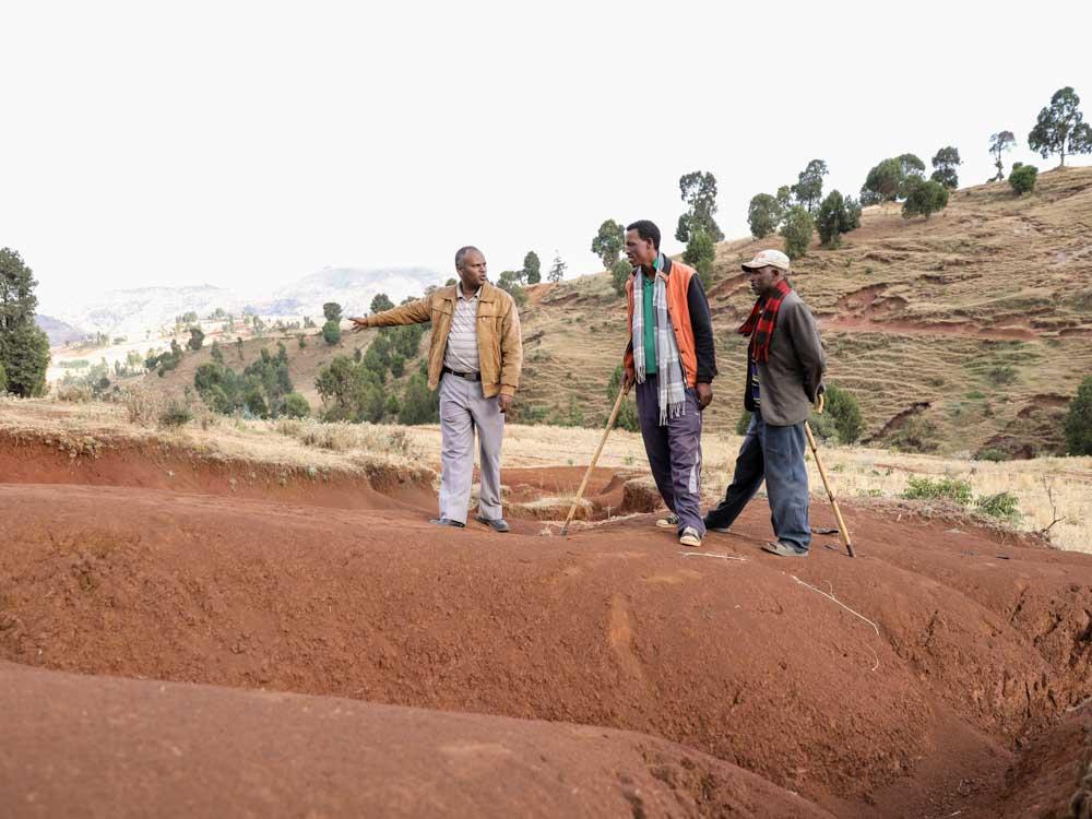 Männer in Äthiopien auf roter Erde untersuchen Boden