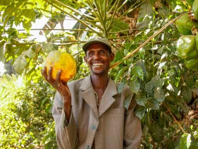 Lächelnder Mann in Äthiopien mit Papaya in der Hand