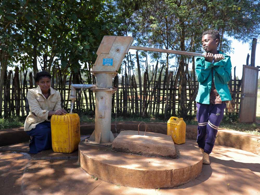 Frau und Junge mit einem gelben Kanister füllen Wasser aus einem Brunnen von Menschen für Menschen ab