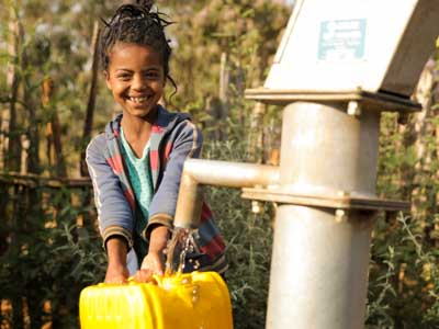 Mädchen mit einem gelben Kanister füllt Wasser aus einem Brunnen von Menschen für Menschen ab