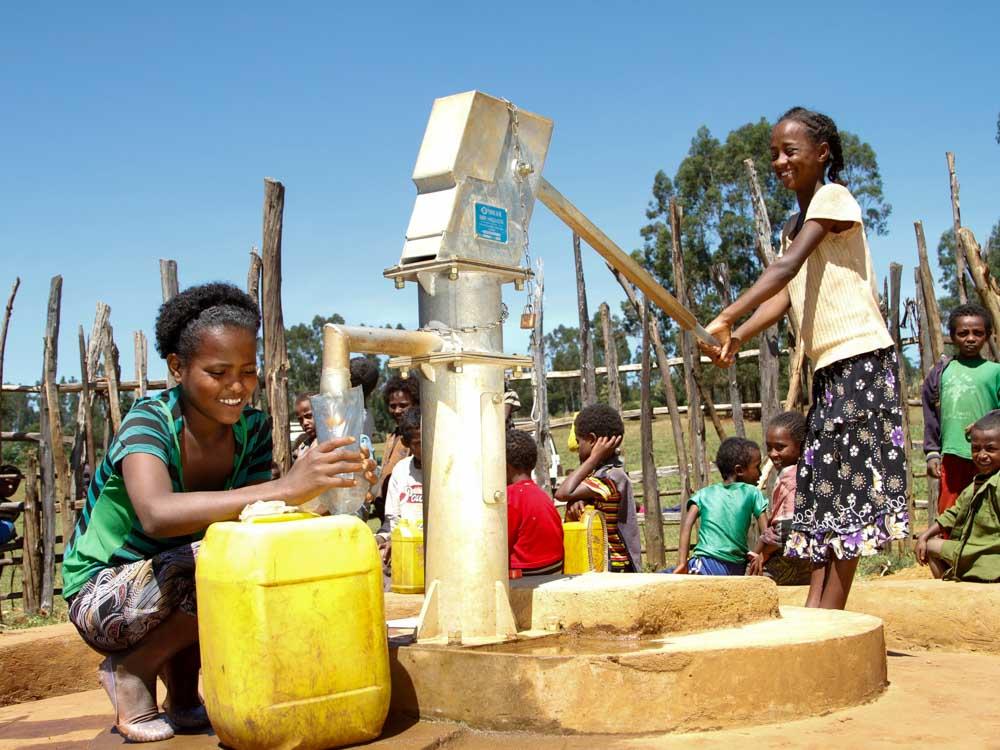 Zwei Mädchen mit einem gelben Kanister füllen Wasser aus einem Brunnen von Menschen für Menschen ab