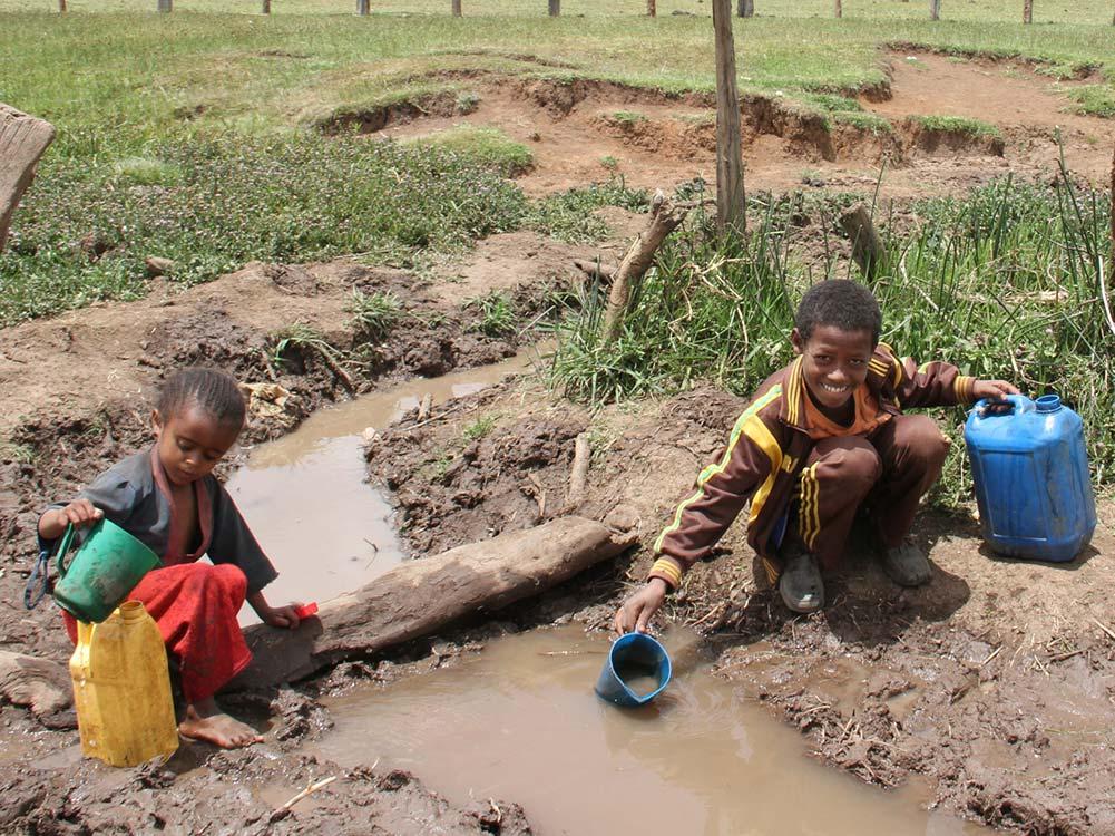 Zwei Kinder schöpfen Wasser aus einer Wasserstelle.
