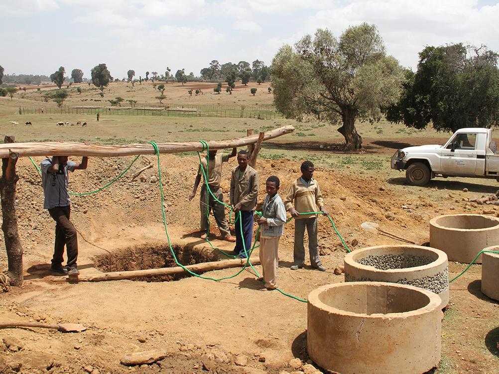 Männer graben einen Brunnen