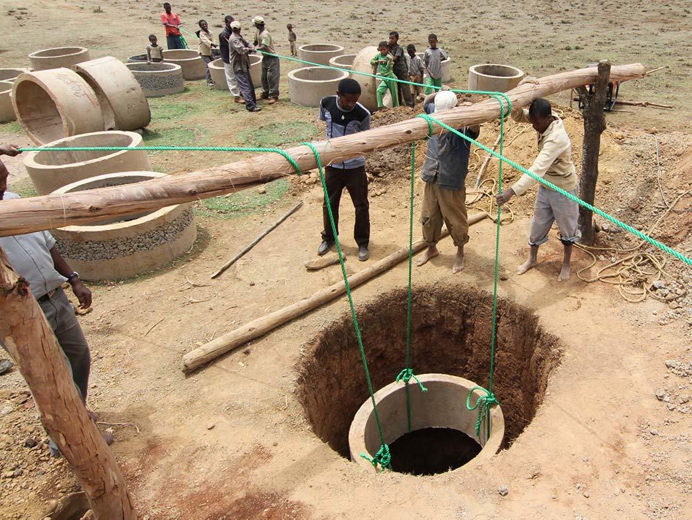 Ein Brunnenring wird an seilen in den Brunnen gelassen
