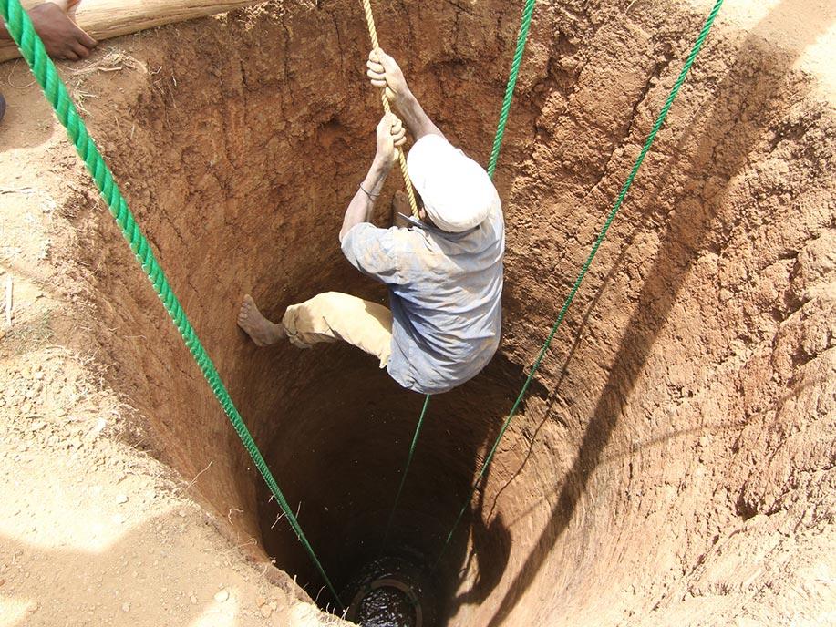 Ein Mann klettert in einen Brunnen.