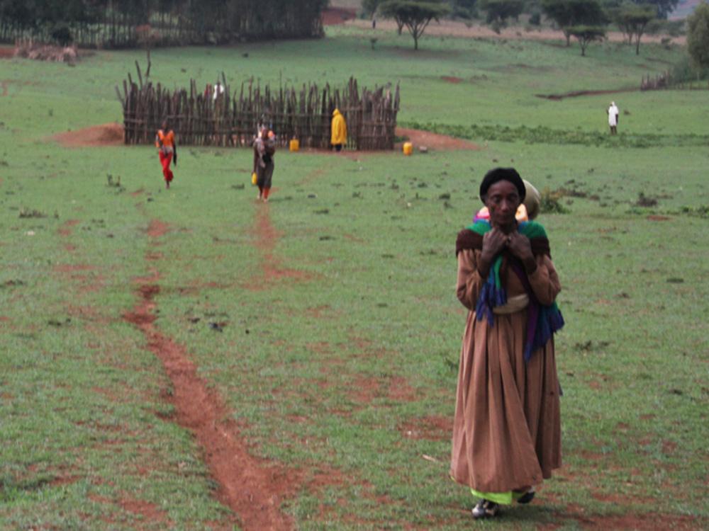 Eine Frau steht vor einem Zaun.