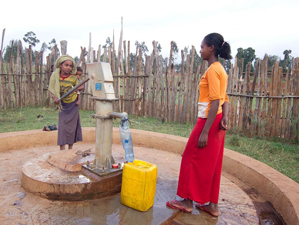 Zwei Mädchen holen Wasser.
