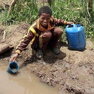 Ein Bub schöpft Wasser aus einer Wasserstelle