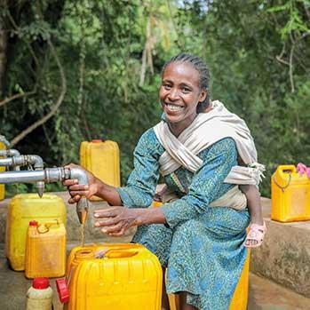 Frau bei einer Quellfassung füllt sich sauberes Wasser in Kanister